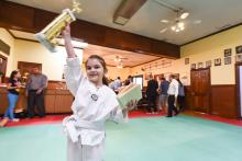 Young US Tae Kwon Do College student raises trophy.