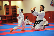 Young US Tae Kwon Do College students breaking a board
