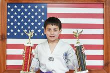 Young US Tae Kwon Do College students displaying trophies.