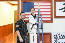 Young US Tae Kwon Do College students displaying trophy.